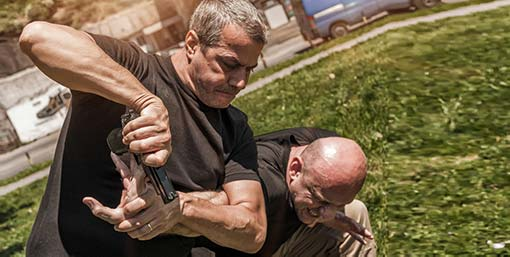 Image of a man using disarming an attacker using techniques learned in Martial Arts Madison , WI classes