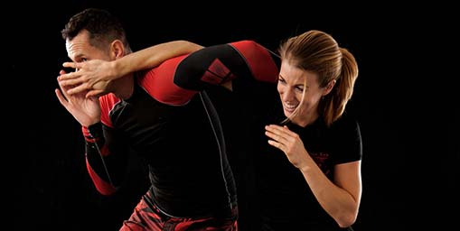 Image of beginner getting pointers from instructor during mma madison classes